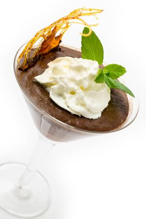 mousse: Homemade chocolate mousse in a martini glass with cream, a sprig of mint and a caramelised sugar decoration