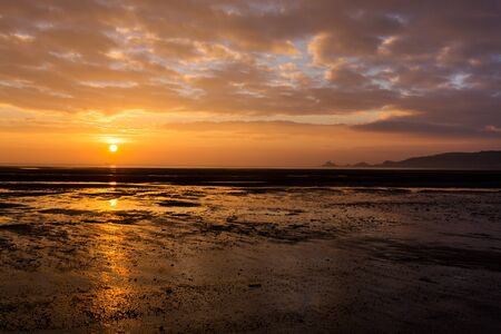 lifeboat: The sun rises out of the sea next to the lighthouse and lifeboat sheds in Mumbles, South Wales, casting a bright reflection on the wet sand and pools left by the receding tide
