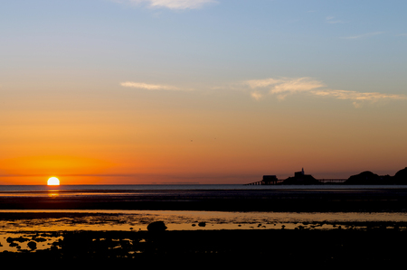 sheds: The sun rises out of the sea next to the lighthouse and lifeboat sheds in Mumbles, South Wales, casting a bright reflection on the wet sand and pools left by the receding tide