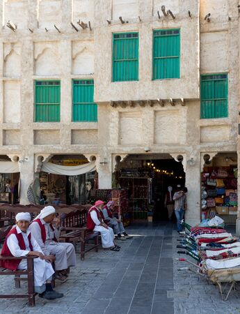 souq: DOHA, QATAR - MARCH 8, 2015: Porters with their barrows await work outside part of the imposing Souq Waqif tourist attraction