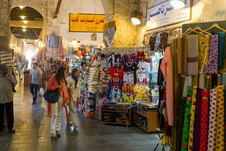 qatar: DOHA, QATAR - MARCH 8, 2015: Shoppers look at the goods in the covered part of Souq Waqif, a popular tourist attraction