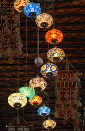 souq: DOHA, QATAR - MARCH 8, 2015: Lanterns strung from the ceiling illuminate the Souq Waqif Arts Centre, with its hanging tapestries and traditional ceiling beams.