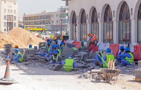 laborers: DOHA, QATAR - MARCH 8, 2015: Asian labourers at work removing a paved area from Souq Waqif, a popular tourist destination in Doha Editorial