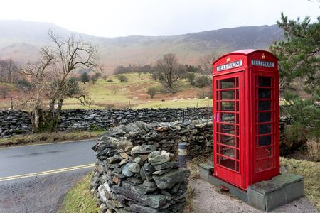 invented: An iconic English telephone box in the Lake District National Park. The phone boxes were once important for communication but fell into disuse after mobile phones were invented. Stock Photo