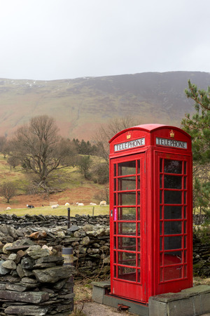 An iconic English telephone box in the Lake District National Park. The phone boxes were once important for communication but fell into disuse after mobile phones were invented. Stock Photo
