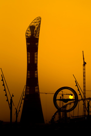 aspire: The sun sets behind the Aspire hotel tower in Doha, Qatar, with cranes involved in work on the Khalifa football stadium on the right, April 2015