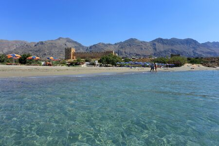 limpid: FRANGOKASTELLO, CRETE - JULY 3, 2016: Tourists relax next to the limpid sea  beside the castle at Frangokastello, south Crete. Visitor numbers on the island were up 12% in July. Editorial