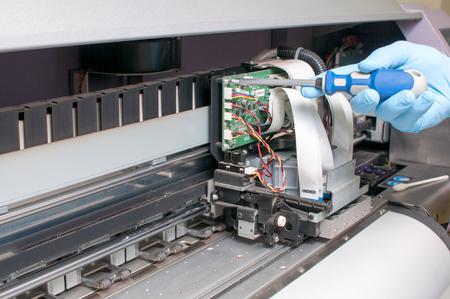 man repairing a printer