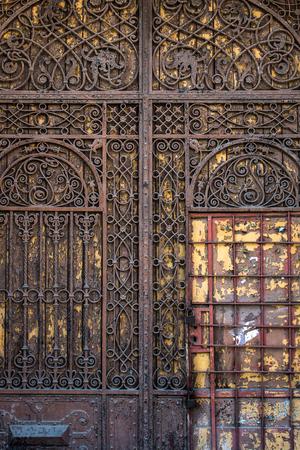 Old wooden door with metal bars