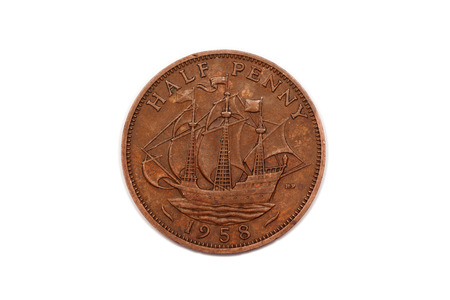 minted: Half penny from the U.K. reverse side and minted in 1958 featuring a ship and  isolated on a white background. Stock Photo