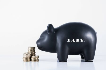 economize: Black piggy bank and some coins with the motif - Baby Stock Photo