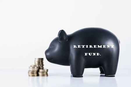 hoard: Black piggy bank and some coins with the motif - Retirement fund Stock Photo
