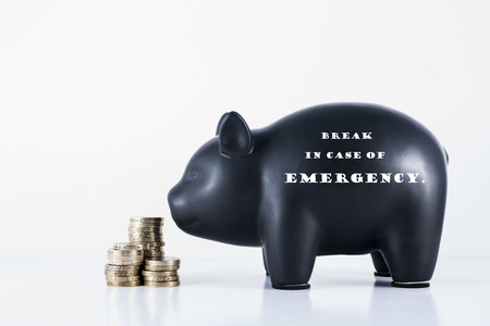 Black piggy bank and some coins with the motif - Break in case of Emergency photo