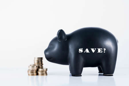 Black piggy bank and some coins with the motif - Save? photo