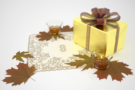 Golden gift box with a bow, autumn leaves and candles. 3d rendering.