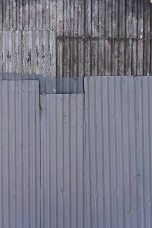 Texture of weathered corrugated sheets of steel riveted together photo