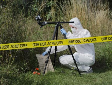 Científico forense comprobación de evidencia detrás de una barrera de la escena del crimen