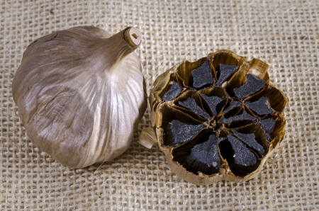 Black garlic bulb with cross section showing black cloves