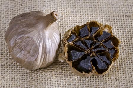 ajo: Bulbo de ajo negro con secci�n transversal que muestra dientes negros Foto de archivo