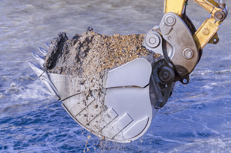 reclamation: Excavator bucket dredging sand and gravel from the seafront