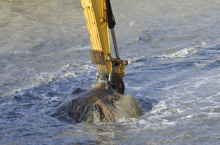 Excavator bucket dredging sand and gravel from the seafront photo