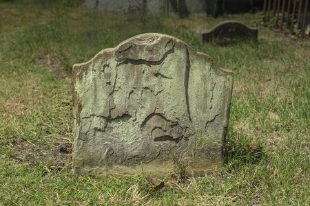 grave: Half buried ancient weathered and flaking gravestone