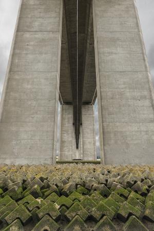 beneath: Beneath a bridge showing geometric blocks with imposing columns Stock Photo