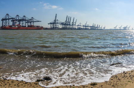 felixstowe: Ship being loaded at a container port that stretches off into the horizon