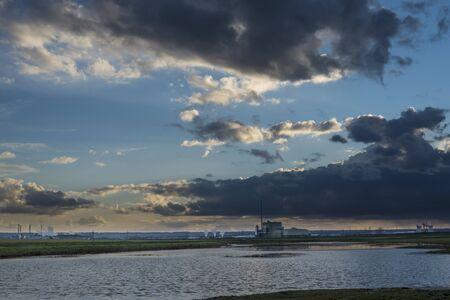 next horizon: Landscape at twilight with an industrial horizon next to a lake Stock Photo