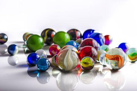 canicas: Grupo de mármoles mezclados en una superficie reflectante de color blanco