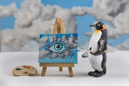 surrealist: Model of a penguin painting a surrealist fish with eye and sky scene