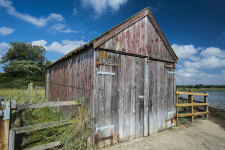boathouse: Old wooden boathouse on the edge of a waterway Stock Photo