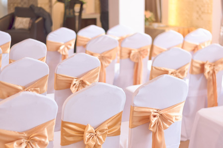 beautiful chairs decoration with ribbon in wedding event hall,selective focus.