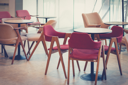 restaurant setting: empty dining table and chair in restaurant setting design with nobody,vintage filter,selective focus. Stock Photo