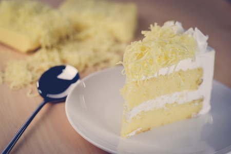 piece of cake with whip cream and grated cheese topping,vintage filter,selective focus.