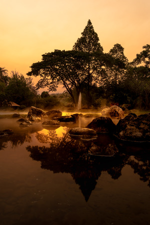 volcanic natural hot spring mineral water pool with steam spa and sun reflect light , travel landmark background ,lampang thailand landscape ,warm dark tone Stock Photo