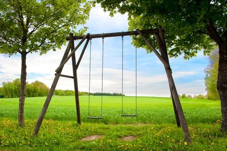 Lone swing seat in a summer field photo