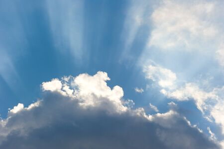 Sun rays streaming trough the clouds photo
