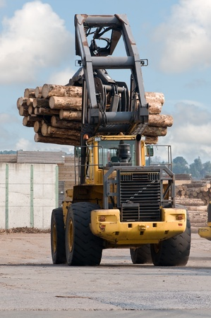logging: Skidder hauling logs at sawmill.