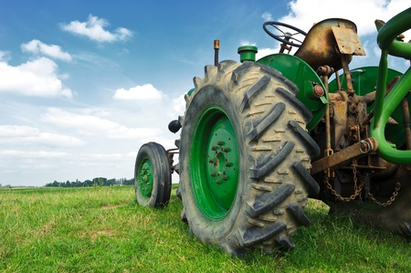 old tractor: Old green tractor in the field with a cloudy sky