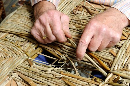 craftsmanship: Man hands making a wicker chair Stock Photo
