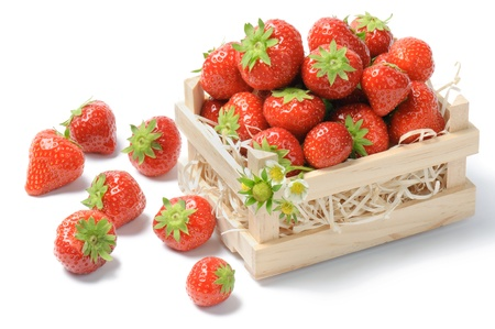 Small wooden crate full of strawberries over white photo