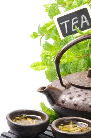 chinese tea ceremony: Asian teapot with green tea and mint background Stock Photo