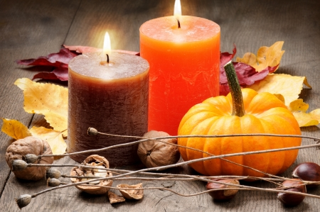 fruit harvest: Autumn setting with candles, pumpkin, walnuts and leaves Stock Photo