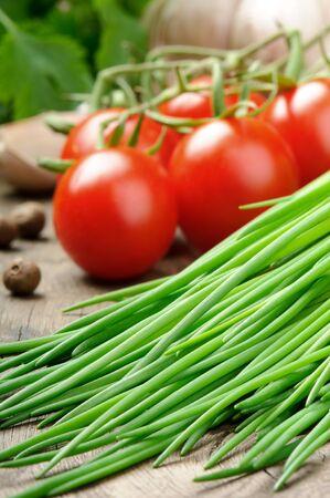 cebollin: De tomates frescos orgánicos cherry y cebollino sobre la mesa de madera