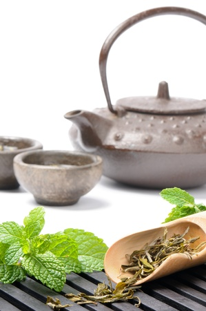 oriental ethnicity: Asian tea set with dried green tea and fresh mint over white Stock Photo