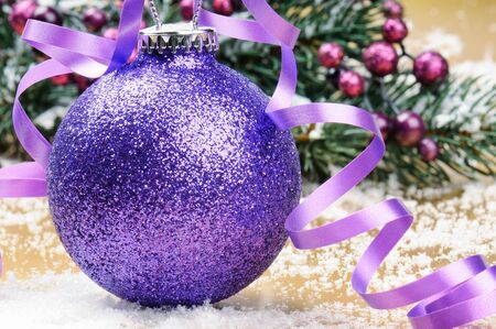 Sparkling purple Christmas ball on a festive background photo