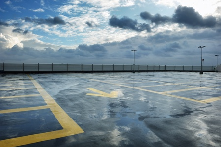 cars parking: Rainy rooftop parking on cloudy day Stock Photo