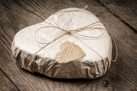 Heart shaped gift on wooden background photo