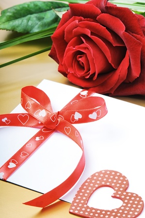 Red rose and envelope in romantic set on golden background photo